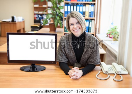 Representative woman sitting at the desk with blank monitor and phones - stock photo