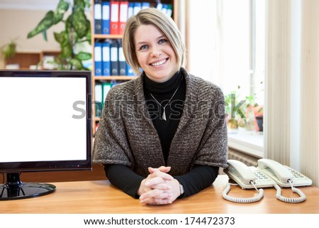 Representative young woman sitting in the office next to the monitor screen - stock photo
