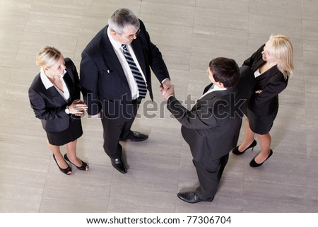 Representatives of two companies shaking hands - stock photo