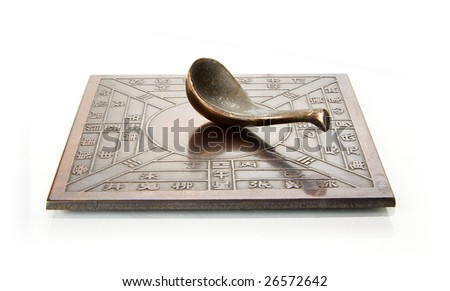 Reproduction of an ancient Chinese compass (which points south) on white background - stock photo