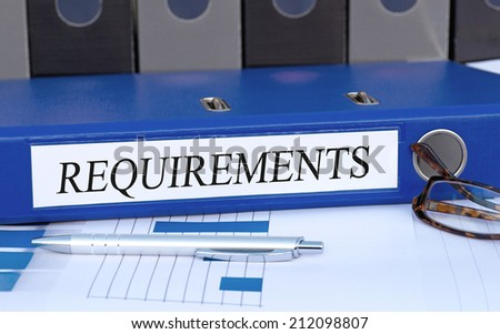 Requirements - blue binder on desk in the office - stock photo