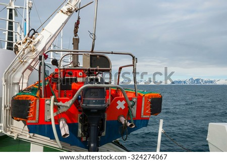 Rescue boat attached on the main ship overlooking the ocean - stock photo
