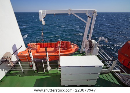 Rescue boat, lifeboat on deck of ship sailing on sea. Photo made wide-angle lens. - stock photo