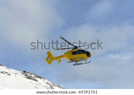 Rescue helicopter in the sky above the Alps - stock photo