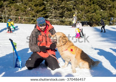 Rescuer and his service dog at Mountain Rescue Service at Bulgarian Red Cross are cheering after successfully rescuing an avalanche victim course, Vitosha mountains, Bulgaria, January 28, 2016. - stock photo