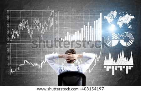 Research concept with businessman sitting in front of wall with forex charts - stock photo