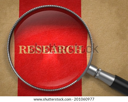 Research Inscription Through a Magnifying Glass on a Red Background - stock photo
