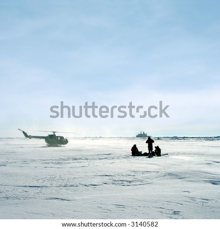 Research team in Antarctica with helicopter and research ship in background - stock photo