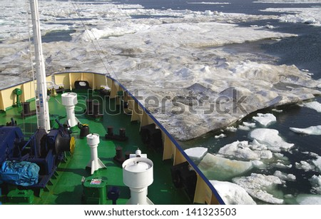 Research vessel in icy arctic sea on a sunny day - stock photo