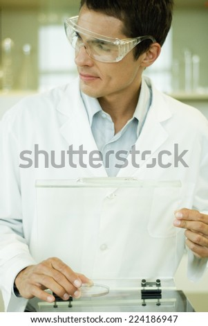 Researcher wearing protective goggles picking up Petri dish, looking away - stock photo