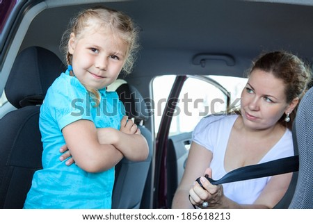 Resentful child ignoring mother forcing to seat into infant car safety seat - stock photo