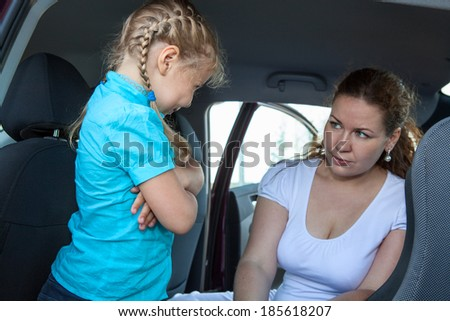 Resentful child refusing get in safety car seat under mother severe look - stock photo