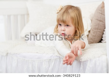 Resentful pretty little girl lies on a sofa in the room. - stock photo