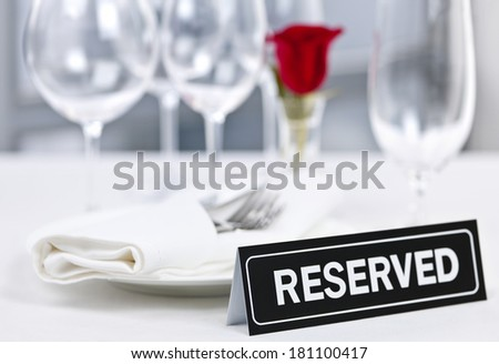 Reserved romantic restaurant table setting with roses plates and cutlery - stock photo