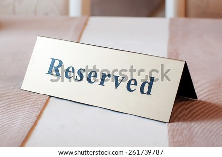 Reserved sign, reservation. On table. Beige - stock photo