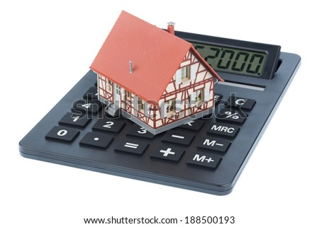 residential building on a calculator, symbolic photo for home purchase, costs and savings - stock photo