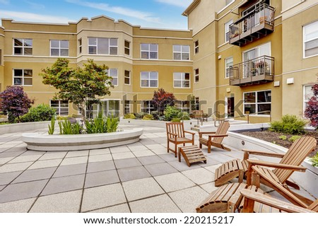 Residential building with spacious courtyard. SItting area with wooden  deck chairs. - stock photo