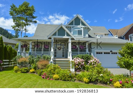 Residential house with patio and garage on blue sky background. Family house in British Columbia, Canada. - stock photo