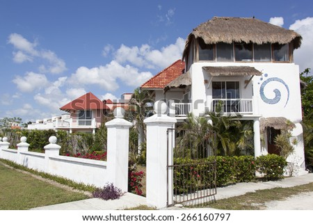 Residential houses with characteristic straw roofs in San Miguel resort town (Cozumel, Mexico). - stock photo