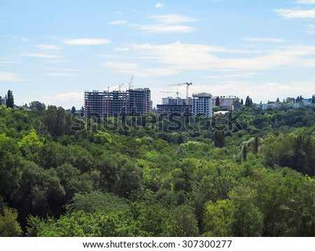 Residential modern apartment house building, green forest and blue sky - stock photo