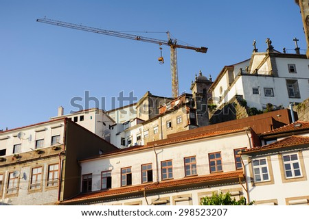 Residential old buildings and building crane rises above them in OPorto, Portugal - stock photo