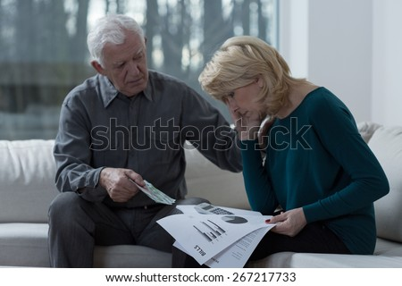 Resigned woman analyzing unpaid bills with her supporting husband - stock photo