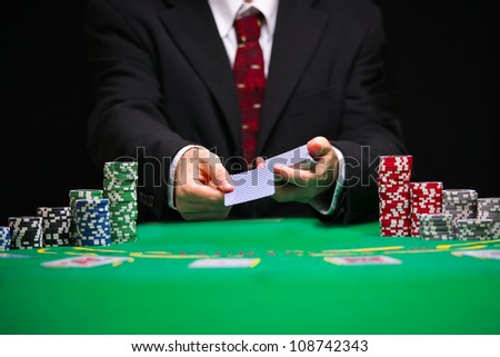 respectable casino worker in a tuxedo with a red tie serving  cards - stock photo