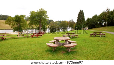 Rest area with many round group tables in a park near a river. - stock photo