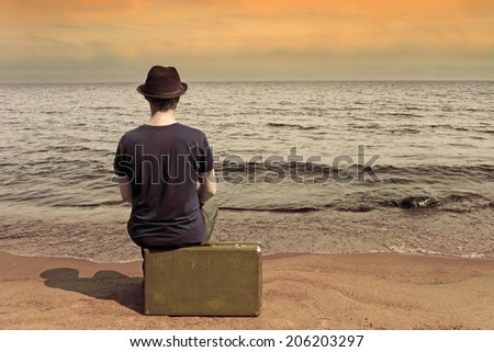 Rest by the sea. The man with a suitcase on a beach in vacation - stock photo