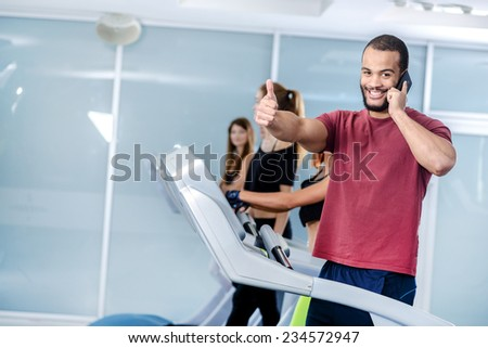 Rest from work. Sport man running on a treadmill and talking on a cell phone bolshory showing thumbs up. Athlete dressed in sports uniforms and running in the gym. - stock photo