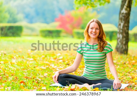 rest in the autumn park. woman practices yoga on the nature - stock photo