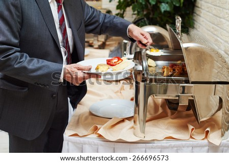 restaurant catering service. Man with food at morning buffet style smorgasbord  - stock photo