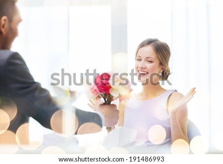restaurant, couple and holiday concept - amazed woman recieving bouquet of flowers from husband or boyfriend at restaurant - stock photo