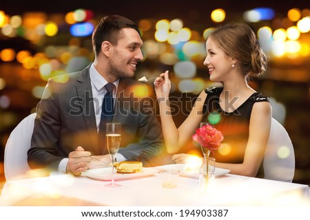 restaurant, couple and holiday concept - smiling couple eating dessert at restaurant - stock photo
