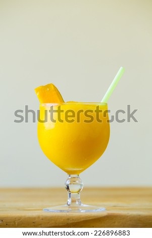 Restaurant drink special at the bar is a yellow mango margarita with a piece of fruit. - stock photo
