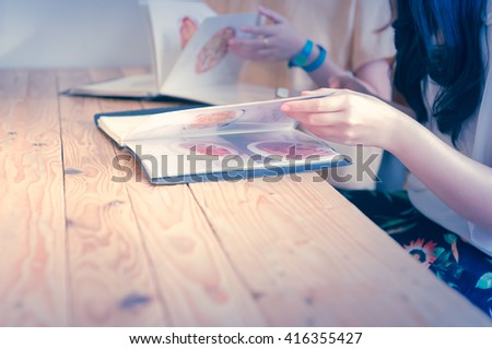 restaurant, food, eating and holiday concept - close up hand one of couple with menu choosing dishes at restaurant - stock photo
