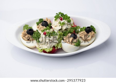 Restaurant food of boiled stuffed eggs with olives and fresh paprika with garnet decorated with parsley and lettuce isolated on white, horizontal picture - stock photo