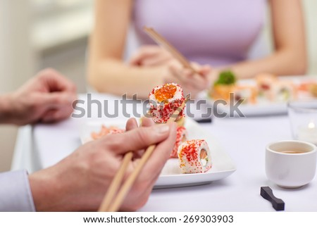 restaurant, food, people, date and holiday concept - close up of couple eating sushi at restaurant - stock photo