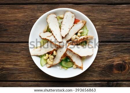 Restaurant food top view. Catering, banquet food. Mediterranean cashew chicken salad.  Roast sliced chicken, turkey meat and cucumbers. Diet, fresh and healthy food. Chicken salad.  - stock photo
