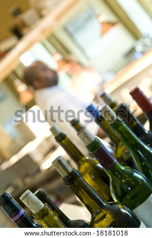 restaurant kitchen with wine bottles in focus in foreground, cook, out of focus in background - stock photo