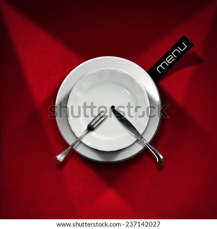 Restaurant Menu Design. Restaurant menu with empty white plate and cutlery, fork and knife, on red velvet background with shadows and black label with written menu - stock photo