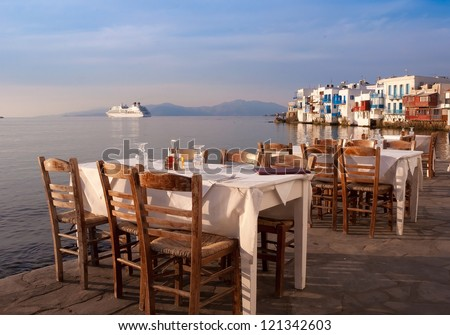 Restaurant near the sea at Little Venice on the island of Mykonos in Greece at sunset - very well-known - stock photo