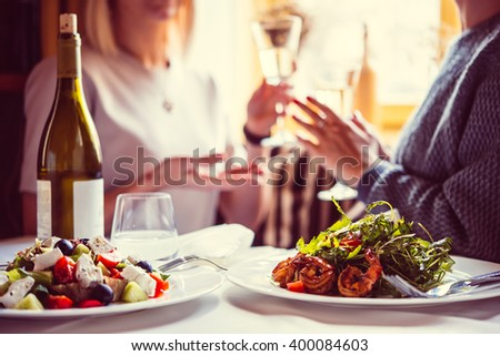 Restaurant or cafe table with plate of salads and wine. Two people talking on background. Toned picture - stock photo