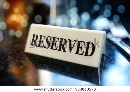 Restaurant reserved table sign with places setting and wine glasses ready for a party - stock photo