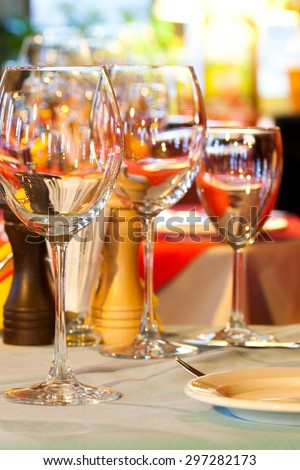 Restaurant service. Served table charger. Wine glasses, plate and cutlery. Bright blurred and soft interior, tableware. romantic evening dinner. vertical. soft focus.  - stock photo