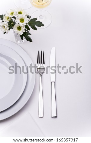 Restaurant table set with white flowers - stock photo