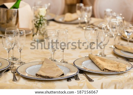 restaurant table with dishes, napkins, glasses and tablecloth - stock photo