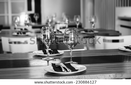 restaurant table with glasses and dish on black and white - stock photo