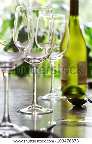 Restaurant table with silverware, white wine and wine glasses - stock photo