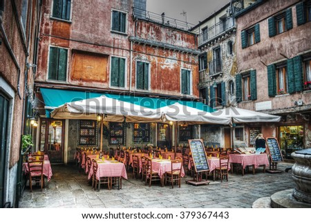 restaurant tables and chairs in a small square in Venice, Italy - stock photo